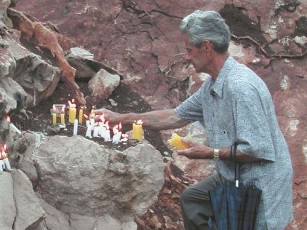 Un fedele albanese accende una candela sulla salita che porta a Lac