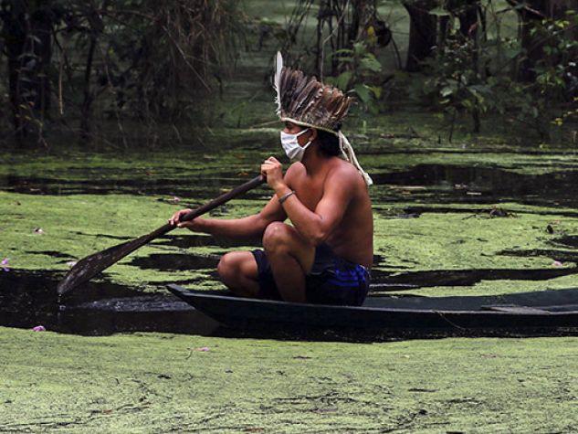 Due indios con mascherine chirurgiche su canoa in un corso d'acqua nella foresta amazzonica.