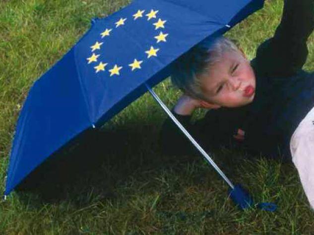 bambino steso su un prato protetto da ombrello con simbolo Unione Europea