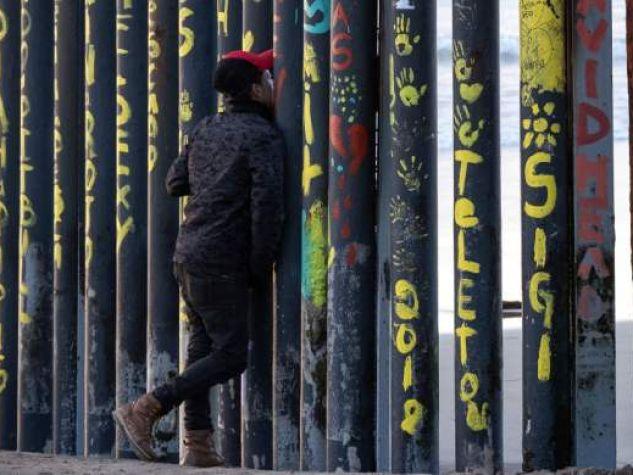 Un uomo guarda attraverso il muro che divide USA e Messico a Playas de Tijuana.