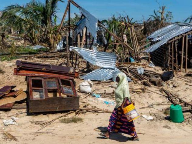 Una donna attraversa il villaggio mozambicano di Guludo, distrutto da un ciclone.