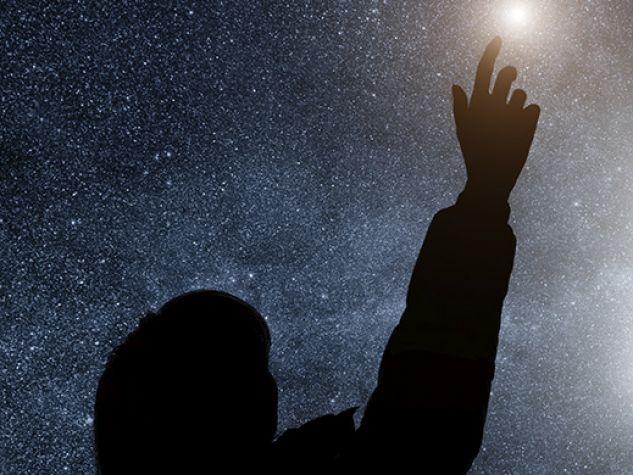 ragazzo allunga la mano come a voler prendere le stelle