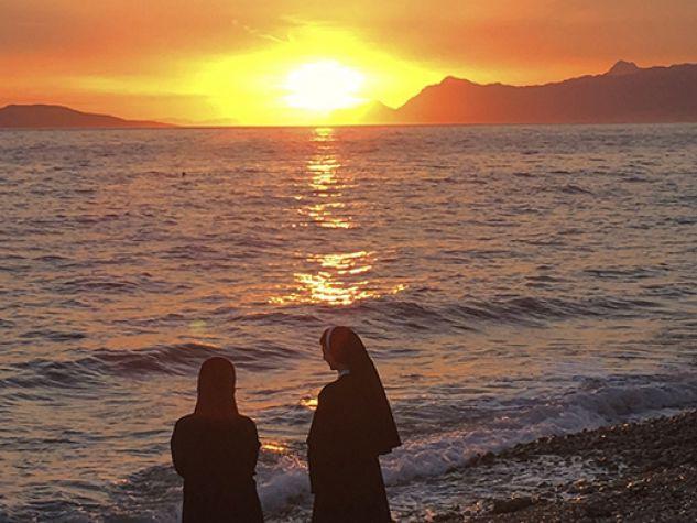 Due suore pregano al tramonto.