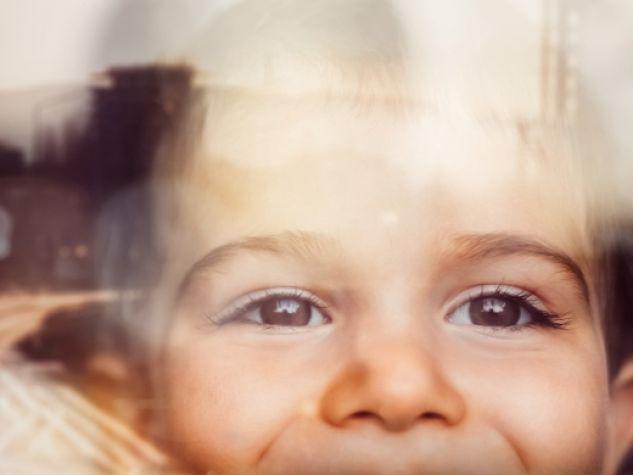 un bimbo sorridente alla finestra
