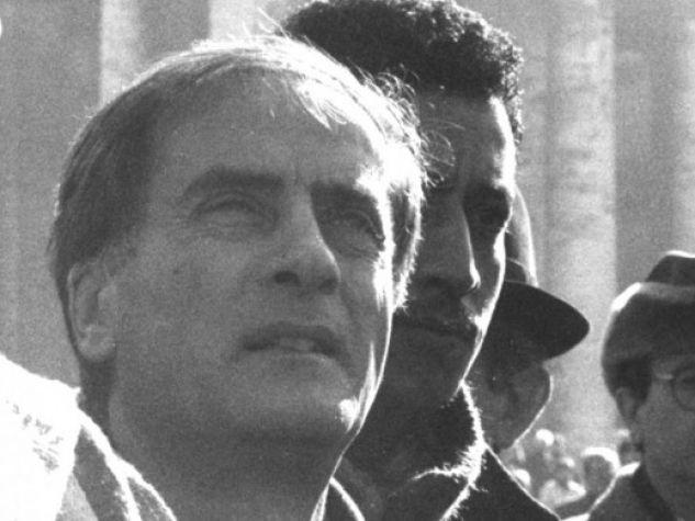 Don Luigi Di Liegro fianco a fianco con alcuni immigrati. Sullo sfondo s'intravvede il colonnato di piazza San Pietro, in Vaticano.