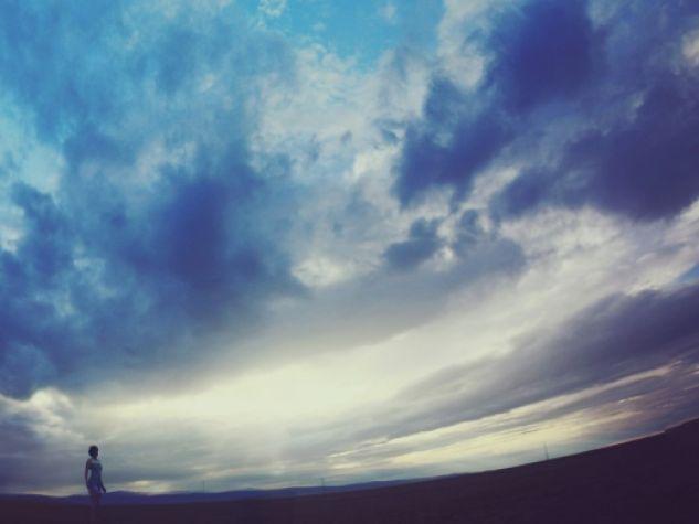 una ragazza nel deserto sovrastata dal cielo
