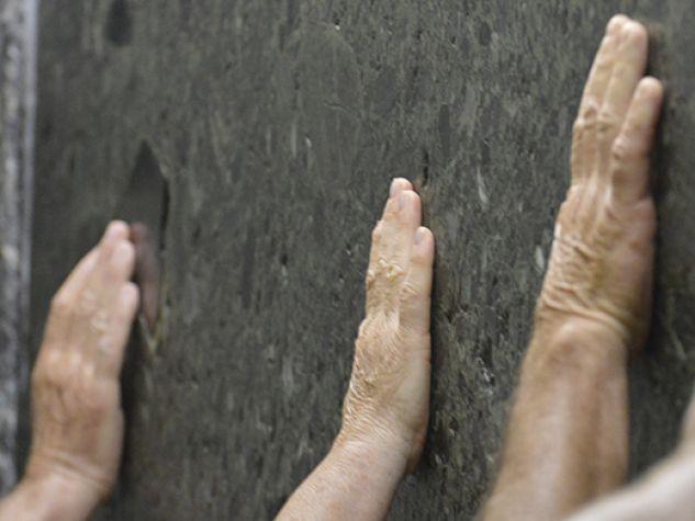 mani che si posano sulla lastra di marmo alla tomba del Santo