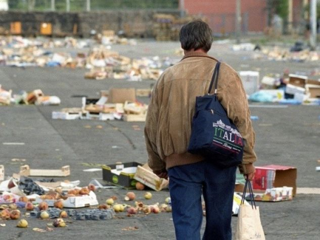 alcuni uomini raccolgono cibo alla chiusura dei mercati generali di Roma