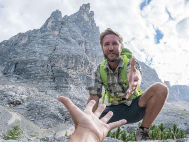 un alpinista tende la mano a un compagno per aiutarlo