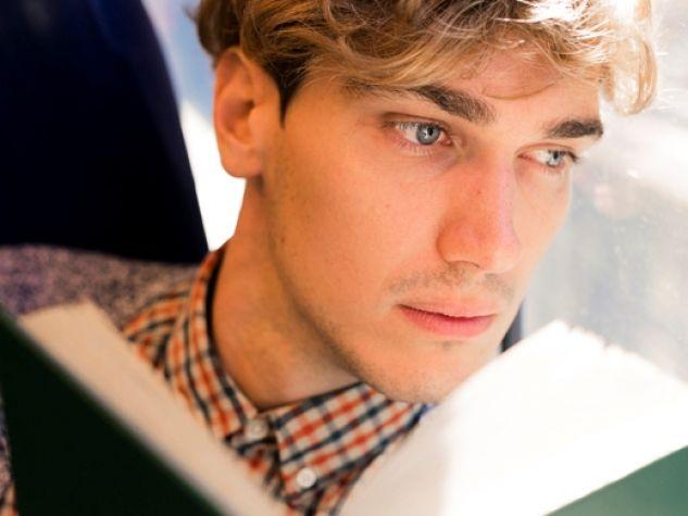 un ragazzo in treno solleva lo sguardo dalla sua lettura