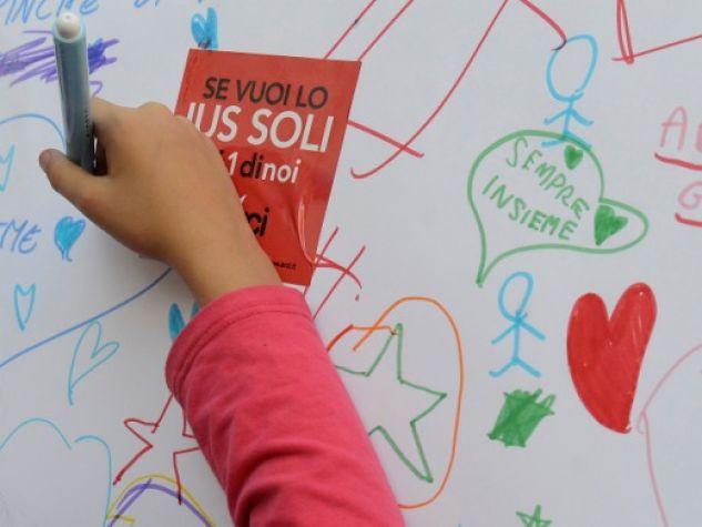 Una bambina scrive un pensiero a favore dello Ius soli nel corso di una manifestazione pubblica