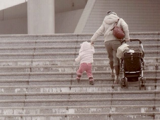 una mamma con bimbo e passeggino sale una scalinata