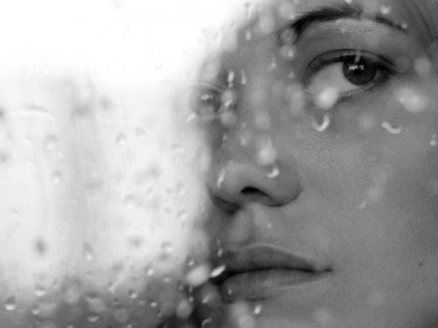 Un volto dietro il vetro imperlato di pioggia