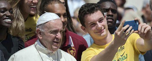 Papa Francesco fa un selfie con un ragazzo.
