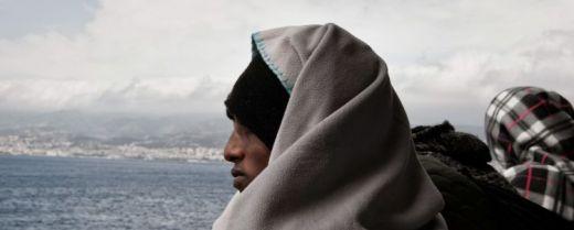 Un migrante scruta l'orizzonte a bordo di una nave.