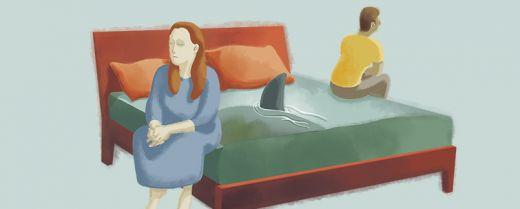 Illustrazione: una coppia seduta sul proprio letto, separata dallo 'squalo' delle incomprensioni