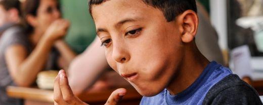 un ragazzo palestinese assapora l'hummus