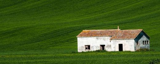 una casa bianca abbandonata nel verde dei campi