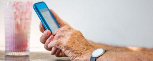 Mani di persona anziana con smartphone