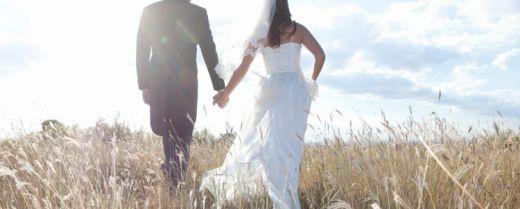 una coppia di sposi cammina su un campo di spighe