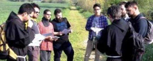 frati e giovani in cammino vocazionale in un momento di preghiera in campagna