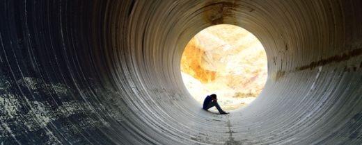 uomo seduto in fondo al tunnel