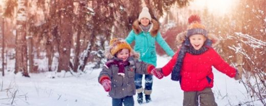 bambini corrono nella neve con la mamma