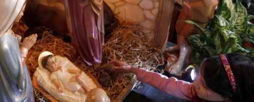 una bimba aiuta a completare il presepe