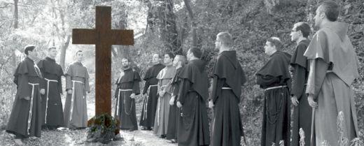 gruppo di giovani frati davanti a un crocifisso