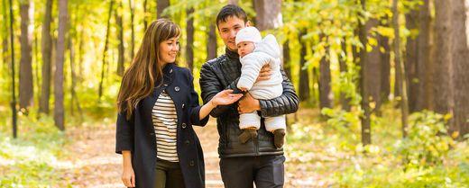 madre padre e figlio camminano in un bosco autunnale