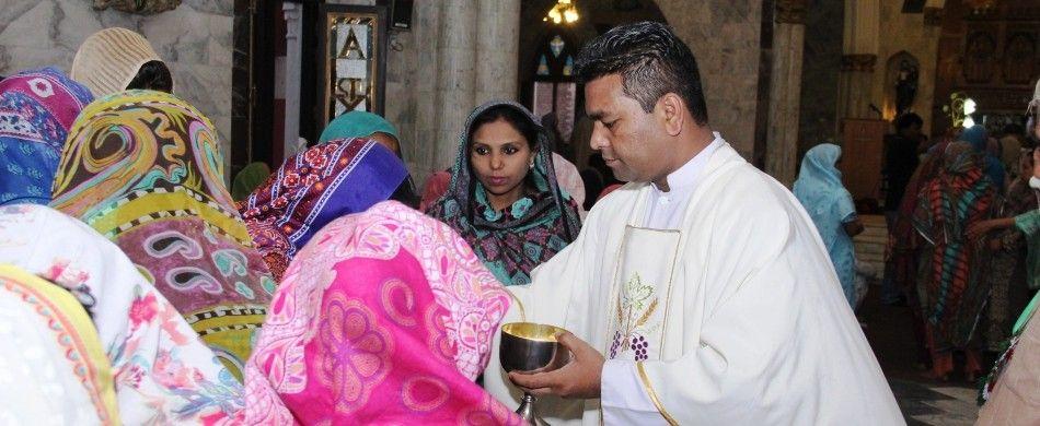 don Iqbal distribuisce l'eucaristia tra i fedeli