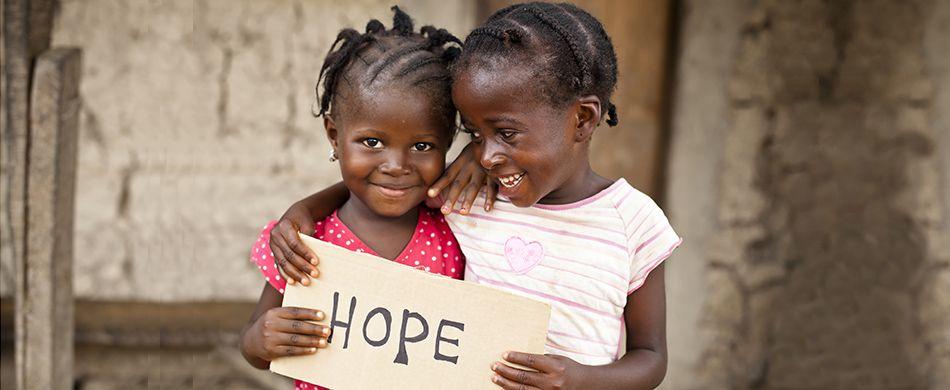 Due bambine africane mostrano un cartello che invita alla speranza.