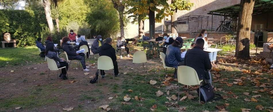 Alcuni studenti del corso di lingua italiana per stranieri seguono la lezione nel giardino interno dell'Antoniano di Bologna, in via Jacopo della Lana.