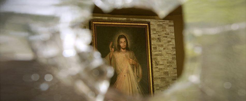 L'immagine di un Cristo, trafitta con armi da fuoco, fotografata attraverso il foro d'ingresso dei proiettili nelle vetrate della chiesa della Divina Misericordia nella capitale nicaraguense