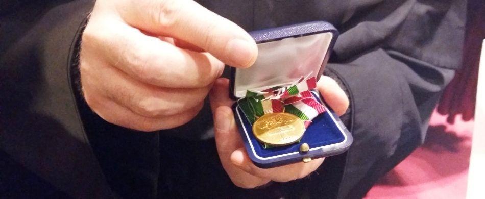 padre Svanera mostra la medaglia ricevuta dal presidente Mattarella