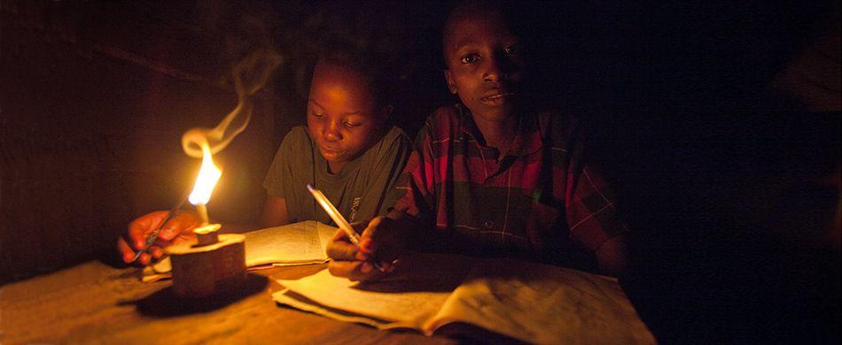 Bambini africani studiano alla fioca luce di una lampada a petrolio