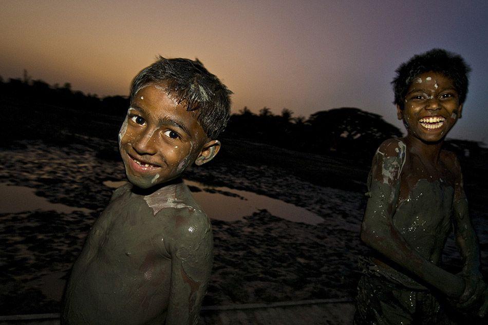 Porto di Chittagong. Due ragazzi giocano con la tipica melma scura, derivata da acque nere e liquami. Il fango, putrido e maleodorante, viene raccolto e utilizzato per la produzione di mattoni. - @Giovanni Mereghetti