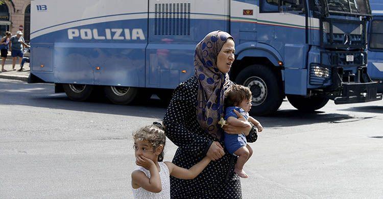 Immigrata con i due suoi figli. Espressione preoccupata.